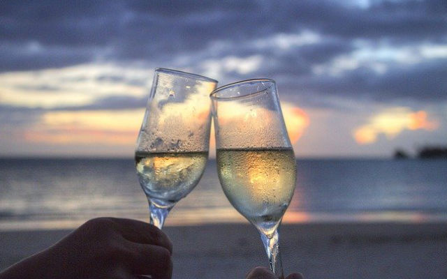 Two champagne glasses toasting in front of a beach