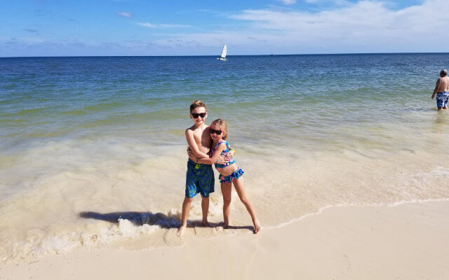 Two children hugging on the beach